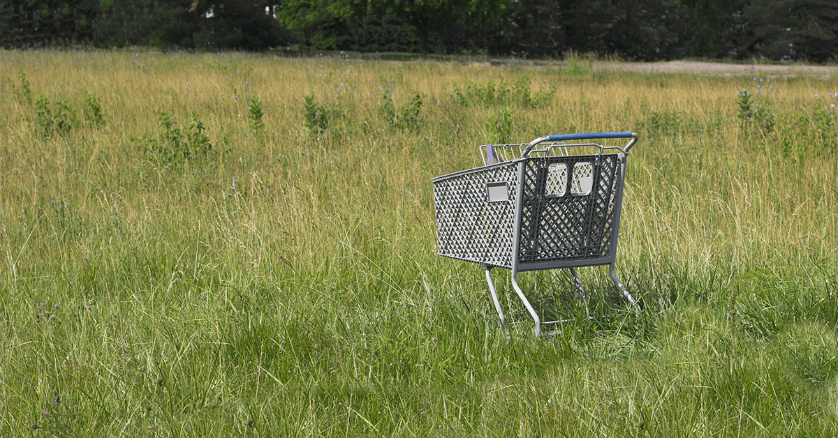Shopping cart abandoned in a field.